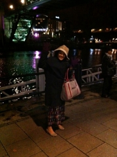 Eaindra wearing two coats by the Tyne in Newcastle
